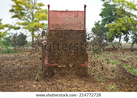 Tractor with trailer fertilizing field with natural manure - stock photo