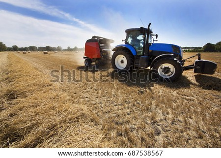 tractor with trailer working to make hay bales with agriculture machine