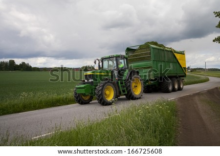 Tractor with wagon and hay - stock photo
