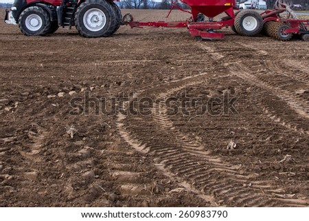 Tractor working on the big large field - stock photo