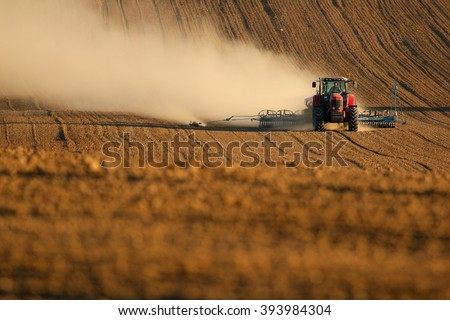Tractor works in field - stock photo