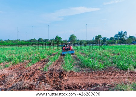 Tractors in the fields. Tractors in sugarcane in  radio tower station the background.  - stock photo