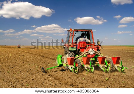 Tractors sowing on agricultural fields on beautiful sunny spring day. - stock photo