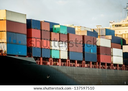 Trade boat carrying containers and arriving at the port