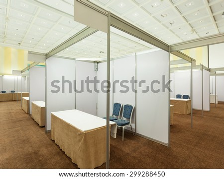 Trade show interior with booth and tables - stock photo