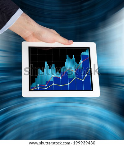 Trader's hand holding a tablet with the forex quotations and rates of the shares in a blue abstract background. - stock photo
