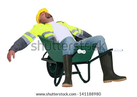 Tradesman asleep in a wheelbarrow - stock photo