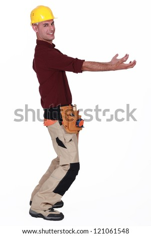 Tradesman carrying an invisible object - stock photo