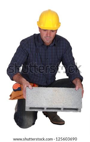 Tradesman holding a clinker block - stock photo