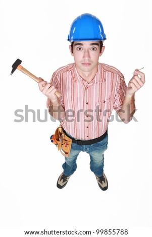 Tradesman holding a hammer and a nail - stock photo