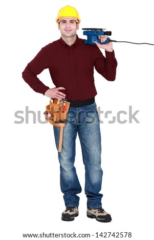 Tradesman holding a sander - stock photo