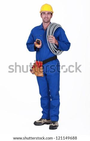 Tradesman holding his tools and corrugated tubing - stock photo