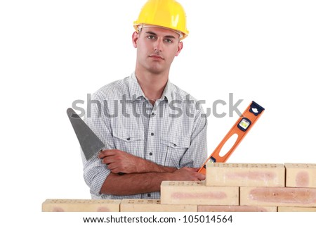 Tradesman holding up a bubble level and a trowel - stock photo