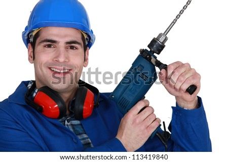 Tradesman holding up an electric screwdriver - stock photo
