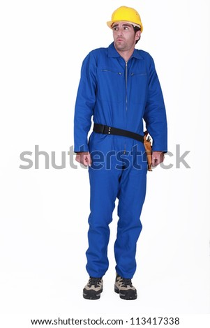 tradesman in blue jumpsuit being scolded - stock photo
