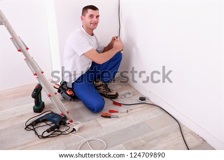 Tradesman installing electrical wiring - stock photo