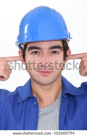Tradesman plugging his ears - stock photo
