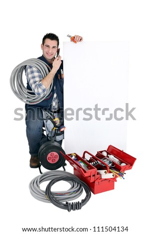 Tradesman posing with a blank sign and his tools - stock photo