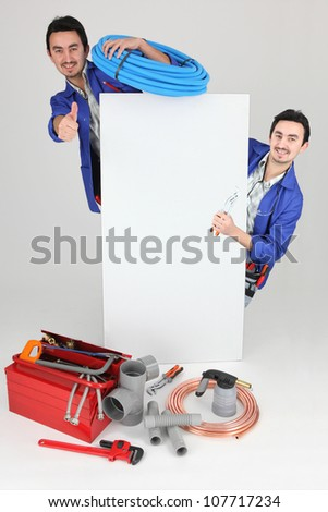 Tradesman posing with his tools and a blank sign - stock photo