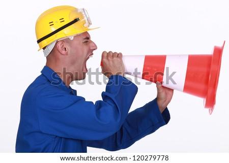 Tradesman screaming into a pylon - stock photo
