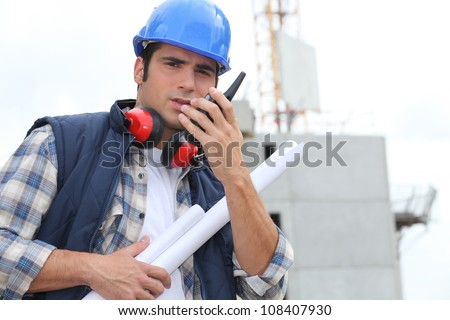 Tradesman speaking into a walkie talkie - stock photo