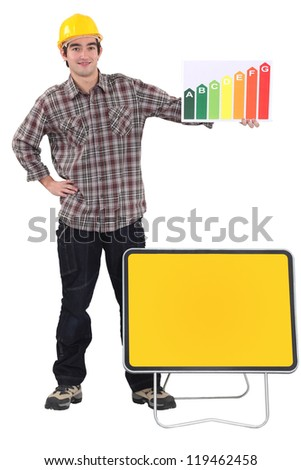 Tradesman standing before a blank sign and holding an energy efficiency rating chart - stock photo