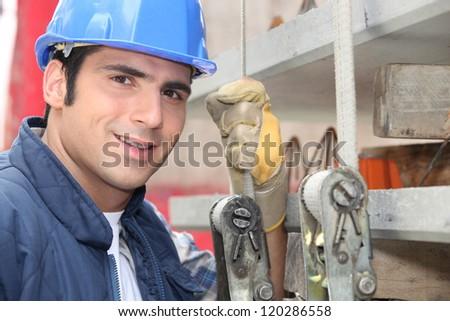 Tradesman standing next to a hoist - stock photo