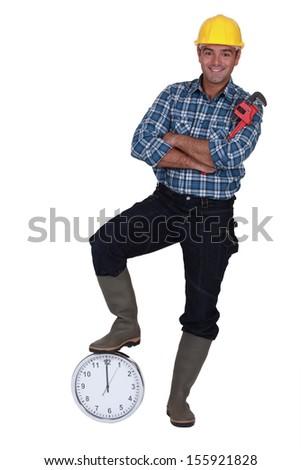 Tradesman stood by a clock - stock photo
