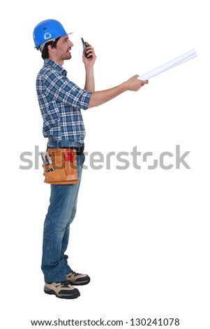 Tradesman trying to communicate with his colleague from a distance - stock photo