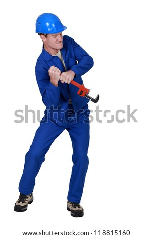 Tradesman trying to force open an object using a pipe wrench - stock photo
