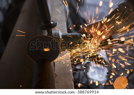 Tradesman uses an electric grinder to cut a pipe in two. Image shows the tool, steel pipe, workman's hand and sparks from the cutting process.