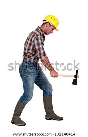 Tradesman using an axe to cut wood - stock photo