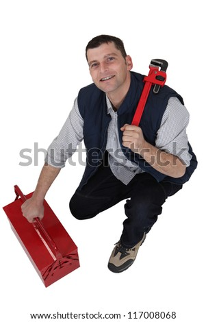 Tradesman with a pipe wrench and toolbox - stock photo