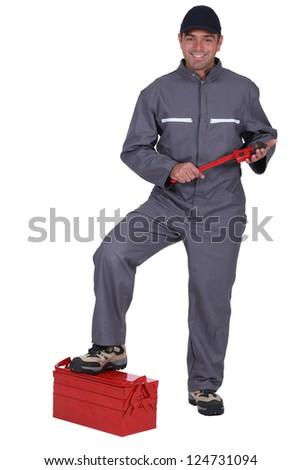 Tradesman with his foot propped on a toolbox - stock photo