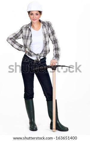 Tradeswoman holding a pickaxe - stock photo