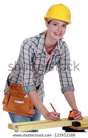 Tradeswoman indicating a measurement on a wooden plank - stock photo
