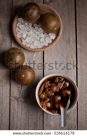 tradional homemade Luo Han Guo Herbal Drink with Ingredients on rustic wooden table top - stock photo