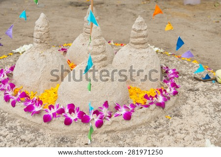 Tradition of carrying sand into the temple or monastery. Prayer flags on sand in Songkran day festival at Thailand. - stock photo