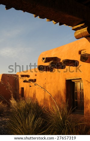 Traditional adobe architecture in New Mexico at sunset - stock photo