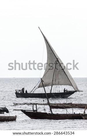 traditional african dhow sailing vessel with full sail to the wind coming into harbor with desaturated color - stock photo