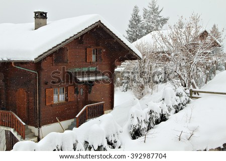 Traditional alpine cabin in the mountains of the Swiss Alps, Switzerland on an overcast day. - stock photo