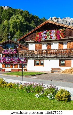 Traditional alpine houses with flowers on balcony, Cortina d'Ampezzo, Dolomites Mountains, Italy - stock photo