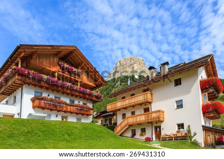 Traditional alpine houses with red flowers on balconies in summer landscape of Dolomites Mountains, Italy - stock photo
