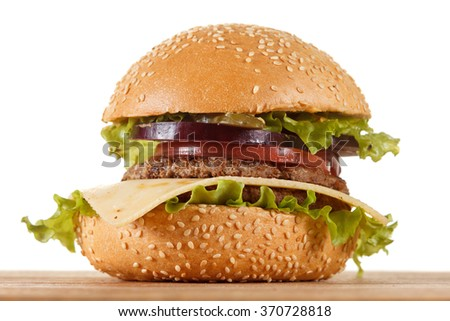 Traditional American cheeseburger. Meat, bun and vegetables closeup on white background