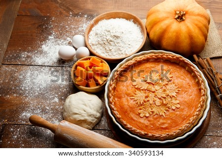 Traditional american fresh round bright orange homemade pumpkin pie in baking dish on wooden table - stock photo
