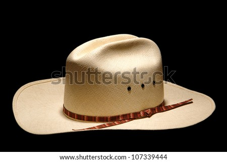 Traditional and authentic American West rodeo cowboy white straw hat with decorative band isolated on pure black background - stock photo
