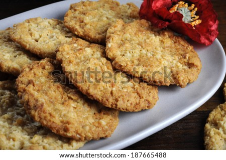 Traditional Anzac biscuits on dark recycled wood with remembrance red poppy for Anzac Day or Remembrance Armistice Day. - stock photo