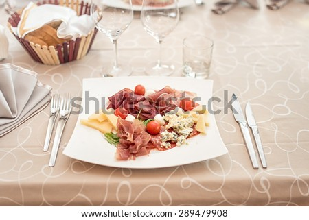 Traditional appetizer with types of ham, prosciutto, mozzarella, cheese, molded parmesan served as starter  - stock photo