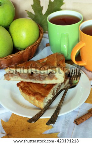 Traditional Apple Pie dessert, yeast dough, brown sugar, cinnamon, raisins, decorated with green apples, dried roses,  tea and autumn foliage on light pastel background, close up view, selective focus - stock photo