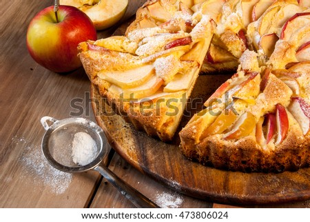 Traditional apple pie on a wooden table, with apple and powdered sugar, close view